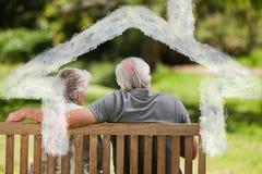 Imagen compuesta de los pares que se sientan en el banco con su de nuevo a la cámara Imágenes de archivo libres de regalías
