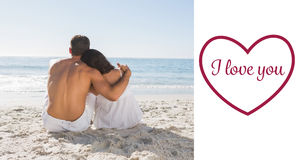 Imagen compuesta de los pares que se sientan en la arena que mira el mar Fotos de archivo