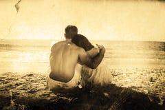 Imagen compuesta de los pares que se sientan en la arena que mira el mar Imagen de archivo