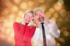 Imagen compuesta de los pares tontos que llevan a cabo corazones sobre sus ojos Imágenes de archivo libres de regalías