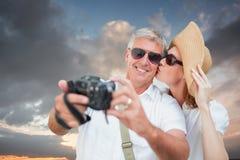 Imagen compuesta de los pares vacationing que toman la foto Fotografía de archivo libre de regalías