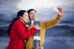 Imagen compuesta de más viejos pares asiáticos en el balcón que toma el selfie Foto de archivo