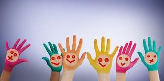 Imagen compuesta de manos con las caras sonrientes coloridas Foto de archivo libre de regalías