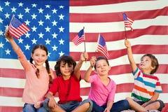 Imagen compuesta de niños con las banderas americanas Fotos de archivo libres de regalías