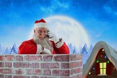 Imagen compuesta de Papá Noel que se coloca al lado de la chimenea y que habla en el teléfono móvil Foto de archivo