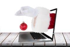 Imagen compuesta de Papá Noel que sostiene la chuchería roja Imagenes de archivo