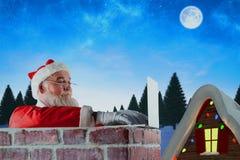 Imagen compuesta de Papá Noel que usa el ordenador portátil en la chimenea Imagenes de archivo