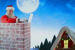 Imagen compuesta de Papá Noel que usa el ordenador portátil en la chimenea Fotografía de archivo libre de regalías