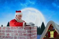 Imagen compuesta de Papá Noel que usa el ordenador portátil en la chimenea Foto de archivo libre de regalías