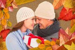 Imagen compuesta de pares casuales en la ropa caliente que sostiene el regalo imagen de archivo libre de regalías