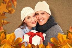 Imagen compuesta de pares casuales en la ropa caliente que sostiene el regalo fotografía de archivo libre de regalías