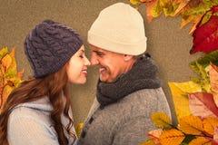 Imagen compuesta de pares en la ropa caliente que se hace frente fotografía de archivo libre de regalías