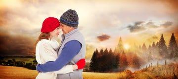 Imagen compuesta de pares felices en el abrazo caliente de la ropa foto de archivo libre de regalías