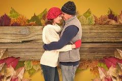 Imagen compuesta de pares felices en el abrazo caliente de la ropa imagenes de archivo