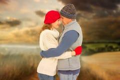 Imagen compuesta de pares felices en el abrazo caliente de la ropa fotografía de archivo