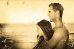 Imagen compuesta de pares felices en el traje de baño que abraza mientras que mira el agua Imágenes de archivo libres de regalías