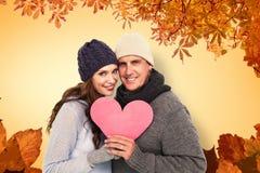 Imagen compuesta de pares felices en la ropa caliente que lleva a cabo el corazón fotos de archivo