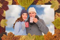 Imagen compuesta de pares felices en la ropa caliente que sostiene las tazas foto de archivo libre de regalías