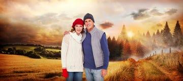 Imagen compuesta de pares felices en ropa caliente fotos de archivo