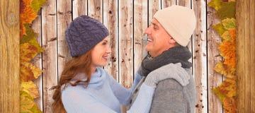 Imagen compuesta de pares felices en ropa caliente imagenes de archivo