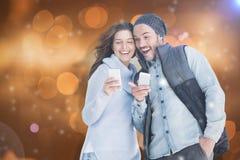 Imagen compuesta de pares jovenes felices usando el teléfono móvil Imagen de archivo