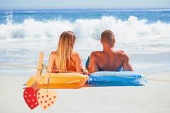 Imagen compuesta de pares lindos en el traje de baño que toma el sol junto Imagen de archivo