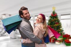 Imagen compuesta de pares sonrientes con el abarcamiento de los panieres Fotos de archivo libres de regalías