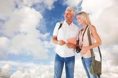 Imagen compuesta de pares turísticos felices usando la guía turística Imagen de archivo