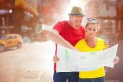 Imagen compuesta de pares turísticos perdidos usando mapa Fotografía de archivo