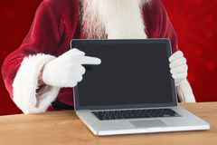 Imagen compuesta de santa feliz que muestra la pantalla del ordenador portátil Fotografía de archivo libre de regalías