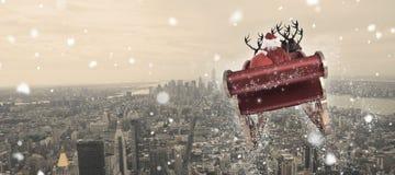 Imagen compuesta de santa que vuela su trineo Foto de archivo libre de regalías