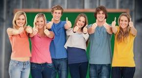 Imagen compuesta de seis amigos que dan los pulgares para arriba como sonríen Imagen de archivo