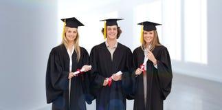 Imagen compuesta de tres estudiantes en el traje graduado que sostiene un diploma Fotos de archivo libres de regalías