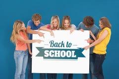 Imagen compuesta de un grupo que sostiene una hoja en blanco y que señala a ella Fotos de archivo