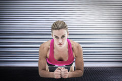 Imagen compuesta de una mujer muscular en una posición del tablón Imágenes de archivo libres de regalías