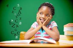 Imagen compuesta del alumno que se sienta en su escritorio imagen de archivo libre de regalías