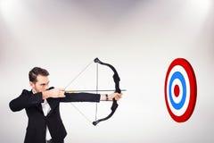 Imagen compuesta del arco y de la flecha elegantes del tiroteo del hombre de negocios Imágenes de archivo libres de regalías