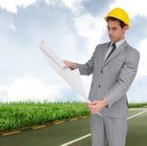Imagen compuesta del arquitecto serio con el casco que mira planes Fotografía de archivo