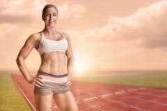 Imagen compuesta del atleta de sexo femenino que presenta con las manos en cadera Fotos de archivo
