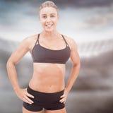 Imagen compuesta del atleta de sexo femenino que presenta con las manos en cadera Imágenes de archivo libres de regalías