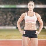 Imagen compuesta del atleta de sexo femenino que presenta con las manos en cadera Imagen de archivo libre de regalías