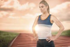 Imagen compuesta del atleta de sexo femenino que se coloca con la mano en cadera Fotos de archivo libres de regalías