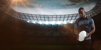 Imagen compuesta del atleta pensativo que sostiene la bola de rugbi que mira abajo de 3D Fotografía de archivo