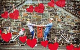 Imagen compuesta del baile joven de los pares de la cadera por la pared de ladrillo con sus bicis Foto de archivo libre de regalías