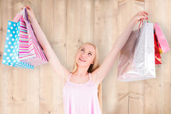Imagen compuesta del blonde bastante joven que sostiene los panieres Fotos de archivo libres de regalías