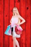 Imagen compuesta del blonde bastante joven que sostiene los panieres Foto de archivo libre de regalías