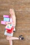Imagen compuesta del blonde bastante joven que sostiene los panieres y los regalos Imagen de archivo libre de regalías