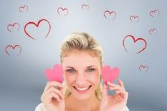Imagen compuesta del blonde joven atractivo que lleva a cabo pequeños corazones Imagen de archivo libre de regalías
