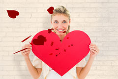 Imagen compuesta del blonde joven atractivo que muestra el corazón rojo Imagen de archivo libre de regalías