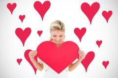 Imagen compuesta del blonde joven atractivo que muestra el corazón rojo Imágenes de archivo libres de regalías